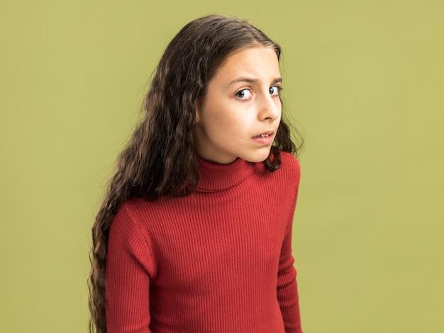 Adolescente dubbioso che sta nella vista di profilo che esamina macchina fotografica isolata sulla parete verde oliva con lo spazio della copia