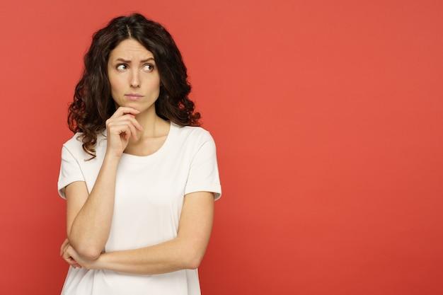 La giovane donna dubbiosa che tocca il suo mento, scettico e pensieroso pensa con le braccia conserte che cerca per copiare lo spazio sopra il fondo rosso dello studio. la ragazza seria sicura riflette sulla domanda o sulla soluzione