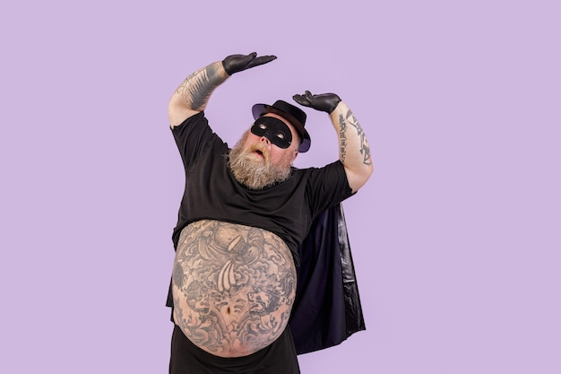 Il dubbioso gentiluomo obeso in costume da eroe si copre dal pericolo superiore su sfondo viola