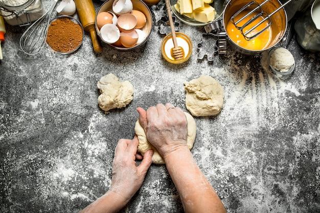 Sfondo di pasta. la donna impasta la pasta con vari ingredienti sul tavolo. su fondo rustico.