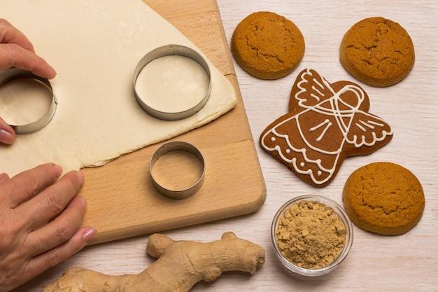 Impasto per cuocere i biscotti allo zenzero su un tagliere, uno stampino per biscotti, le mani tagliate i biscotti dall'impasto