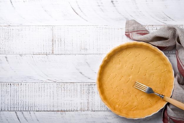 Impasto per cuocere quiche, crostata o torta in forma di cottura in ceramica pronta per la cottura su carta assorbente da cucina su fondo di legno della vecchia tavola rustica bianca. vista dall'alto, copia dello spazio. concetto di cottura fatta in casa per le vacanze.