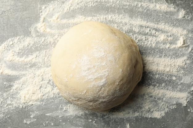 Sfera di pasta e farina su sfondo grigio