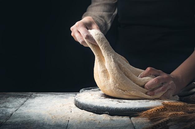 Impasto nelle mani di una donna cucinare su uno sfondo di legno