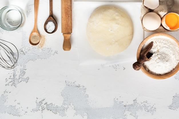 Impasto e ingredienti per la preparazione di pasta, pasta, uova, farina, acqua e sale su un vecchio tavolo rustico leggero