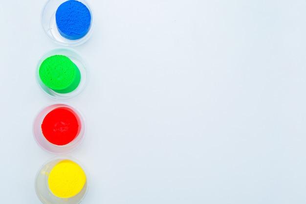 L'impasto per modellare i colori rosso giallo blu e verde viene disposto in fila verticale in vasetti sul...