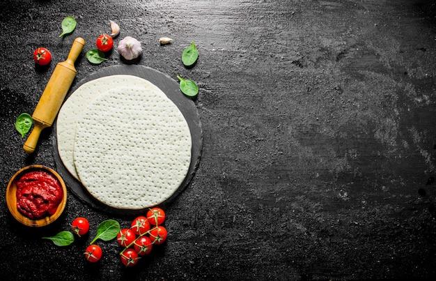 Impasto con vari ingredienti per cucinare la pizza fatta in casa. su sfondo nero rustico