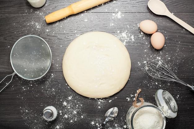 Pasta su uno sfondo di legno con strumenti di cottura