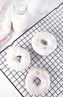 Ciambelle sulla griglia glassata alla crema o glassa al cioccolato bianco e imbottigliare con il latte sullo sfondo.