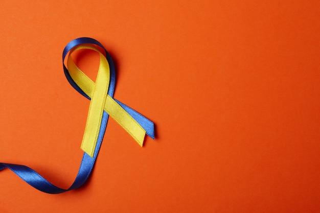 Nastri di consapevolezza della sindrome di down su sfondo arancione