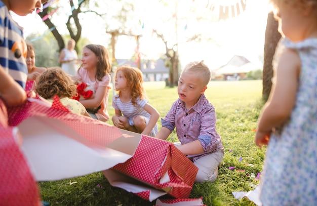 Sindrome di down bambino con gli amici alla festa di compleanno all'aperto in giardino, aprendo i regali.