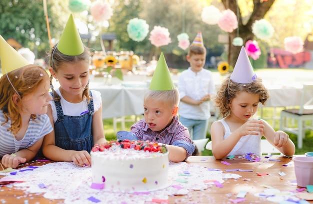 Sindrome di down bambino con gli amici sulla festa di compleanno all'aperto in giardino in estate.