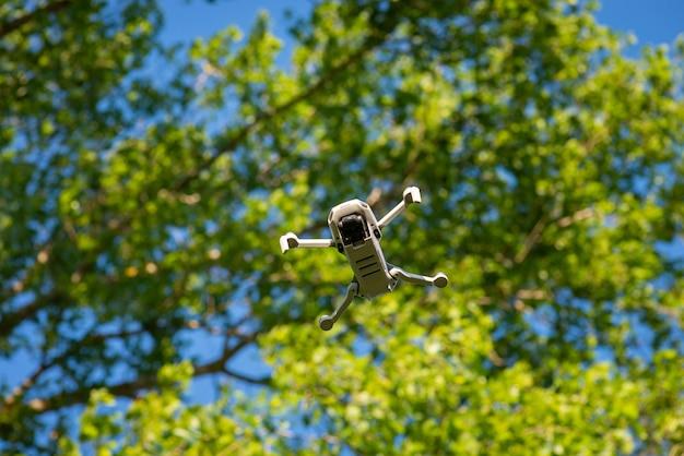 Vista in basso di aerei in volo in aria. drone avanzato contro gli alberi verdi