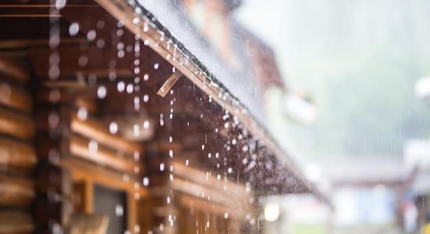 Acquazzone nel temporale estivo e gocce di pioggia sul tetto.