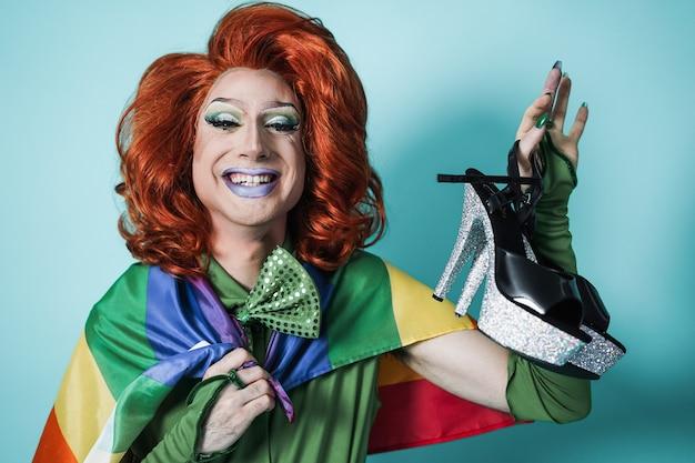 Drag queen con bandiera arcobaleno e tacchi alti - concetto lgbtq - focus on face