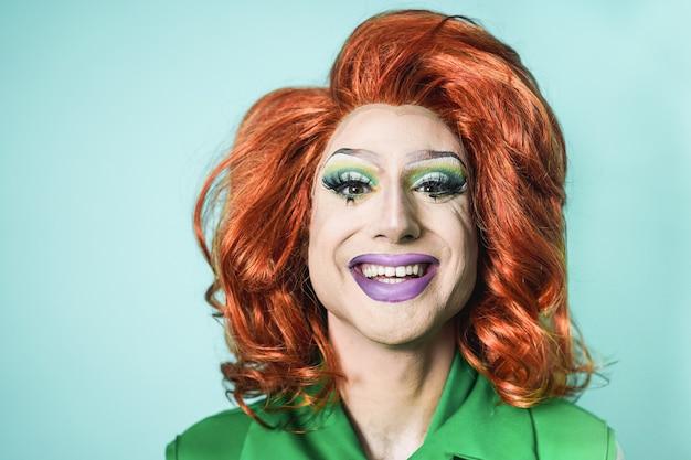 Drag queen sorridente sulla fotocamera con sfondo turchese - concetto lgbtq - focus on face