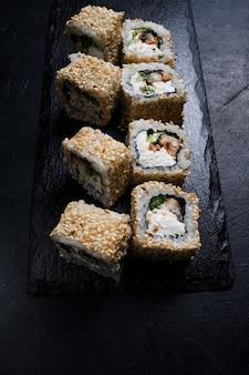 Involtini di sushi di anguilla del drago in semi di sesamo