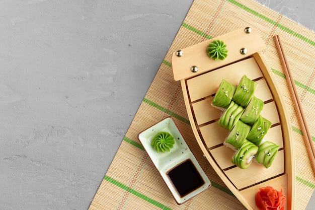 Rotolo di sushi del drago coperto con pezzi di avocado si chiuda