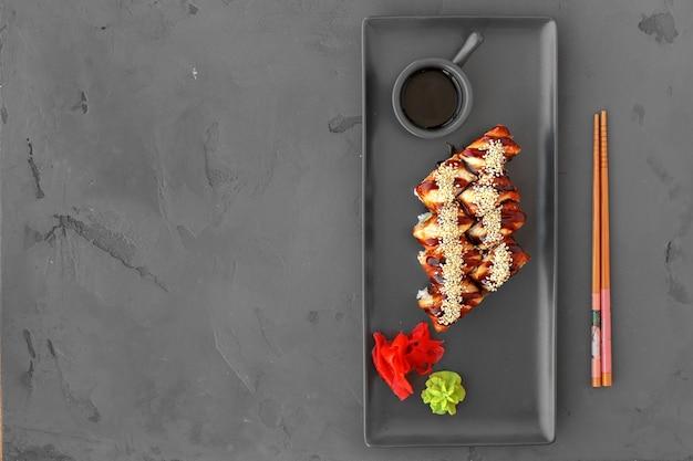 Rotolo di sushi del drago con l'anguilla sulla vista superiore del fondo grigio