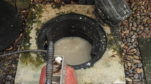 Pulizia degli scarichi. idraulico che ripara la trappola del grasso intasata con la macchina della coclea manutenzione del sistema fognario e del degrassatore da parte di un idraulico professionista. usando il serpente a coclea per riparare e sbloccare uno scarico.