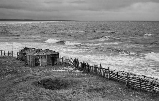 Drammatico paesaggio marino in bianco e nero con un mare bianco impetuoso e una capanna di pescatori sulla riva. baia di kandalaksha. umba. russia.