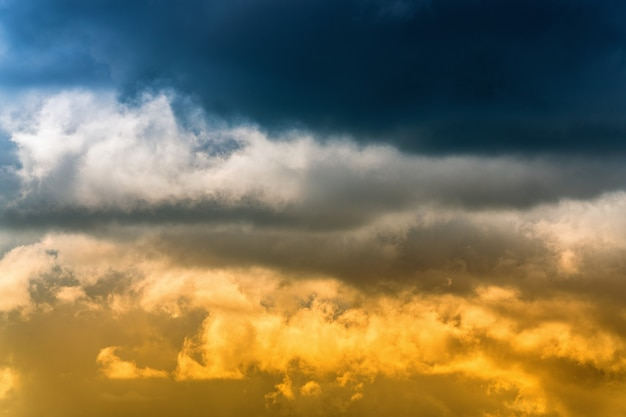 Drammatiche nuvole temporalesche blu in alto e soffici nuvole giallo-dorate illuminate dai raggi del sole in basso. splendida vista sullo sfondo di meteorologia naturale. incredibile cloudscape per cambiare il tempo prima della pioggia.
