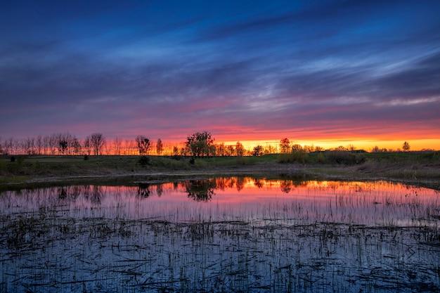 Alba luminosa drammatica o tramonto sul lago Foto Premium