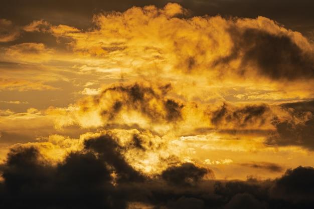 Nuvole drammatiche illuminate il sorgere del sole nel cielo per cambiare il tempo. sfondo di condizioni meteorologiche naturali. messa a fuoco morbida, sfocatura del movimento. immagine cloudscape pronta per il design, sostituisci il cielo nell'editor di foto.
