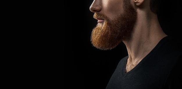 Foto del primo piano della barba di concetto drammatico. ritratto di giovane uomo barbuto bello in attesa. studio girato su sfondo nero