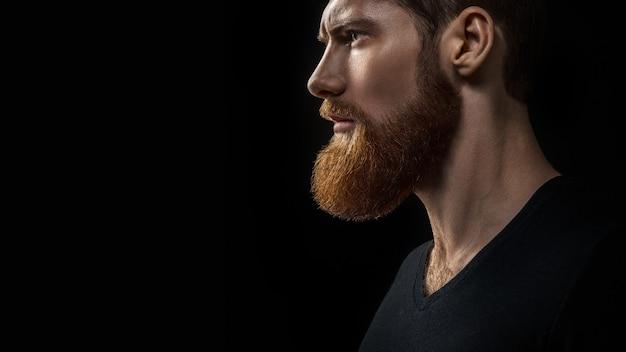 Concetto drammatico ritratto del primo piano di giovane uomo barbuto bello in attesa. studio girato su sfondo nero