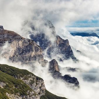 Vista drammatica del paesaggio con le montagne rocciose coperte di nuvole tempestose, dolomia, italia