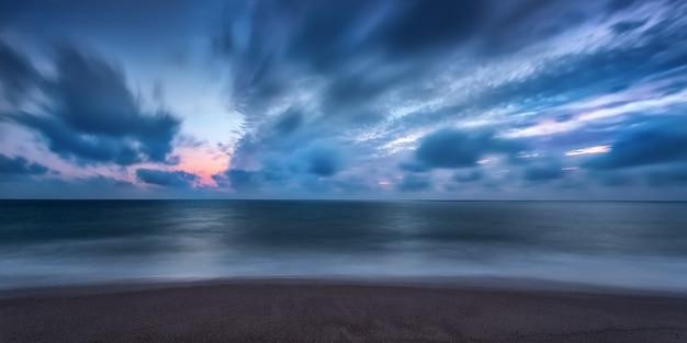 Drammatica vista sul mare a lunga esposizione sulla spiaggia di faro, portogallo.