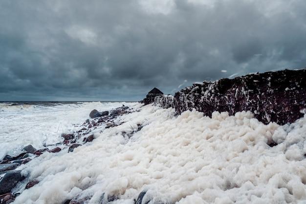 Drammatico paesaggio marino tempestoso minimalista con onde e schiuma bianca sul mare bianco.