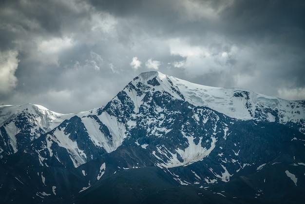 Drammatico paesaggio di montagne con grande cresta di montagna innevata sotto il cielo nuvoloso. scenario scuro dell'altopiano atmosferico con alta catena montuosa con tempo nuvoloso. grandi montagne impressionanti sotto le nuvole grigie.