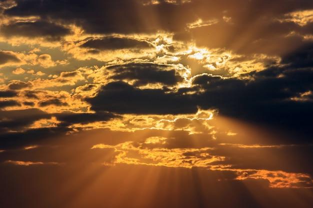 Drammatico cielo arancione con nuvole scure e raggi del sole al tramonto