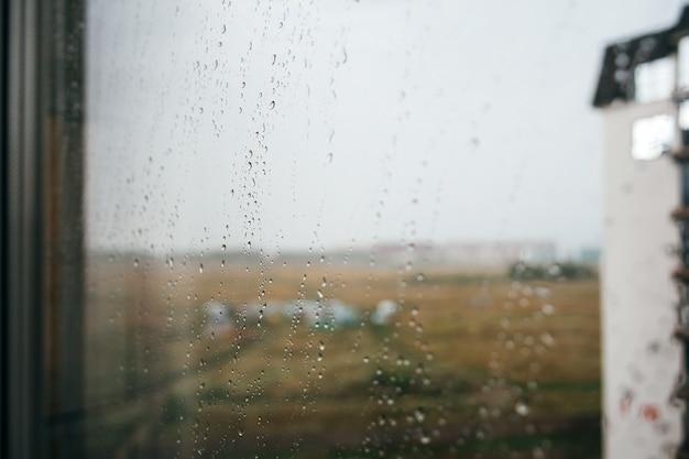 Foto drammatica durante la pioggia: vista sfocata attraverso una finestra di vetro con gocce d'acqua all'angolo di una casa vicina e un ampio campo. autunno, tempo depressivo e piovoso. messa a fuoco selettiva