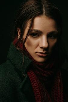 Drammatico ritratto di ragazza in cappotto e sciarpa