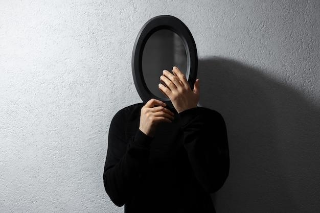Drammatico ritratto di giovane uomo con specchio ovale nero sul viso