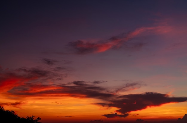 Il cielo rosso e arancione drammatico e le nuvole astraggono il fondo nuvole arancioni sul cielo al tramonto