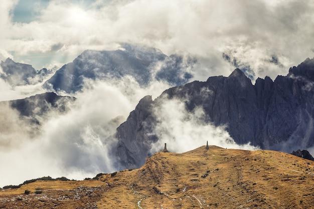 Montagne rocciose drammatiche nelle nuvole e nel sole che splendono, dolomia, italia