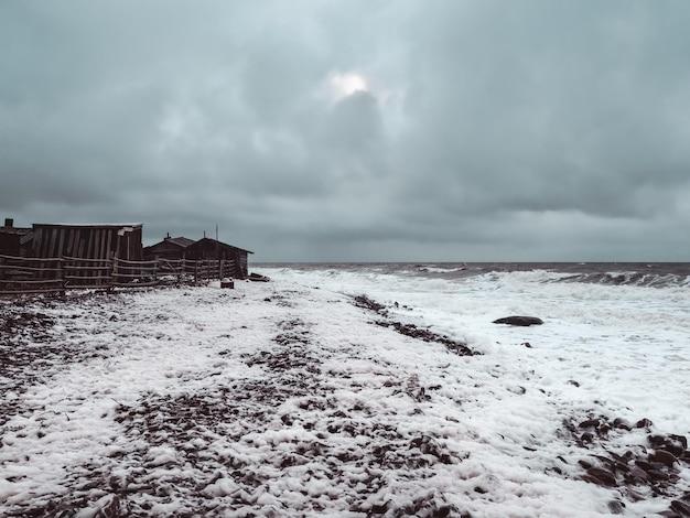 Drammatico paesaggio marino con un mare bianco impetuoso e una capanna di pescatori sulla riva. baia di kandalaksha. umba. russia.