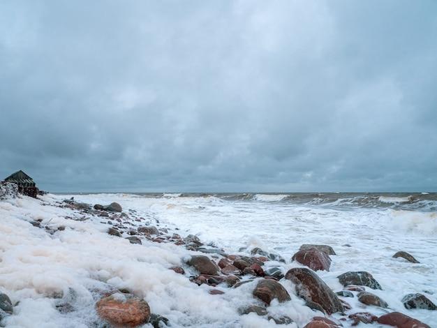 Drammatico paesaggio marino con un mare bianco impetuoso e una capanna di pescatori sulla riva