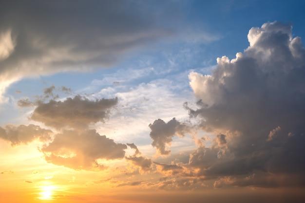 Cielo drammatico al tramonto con nuvole gonfie illuminate dal tramonto arancione.