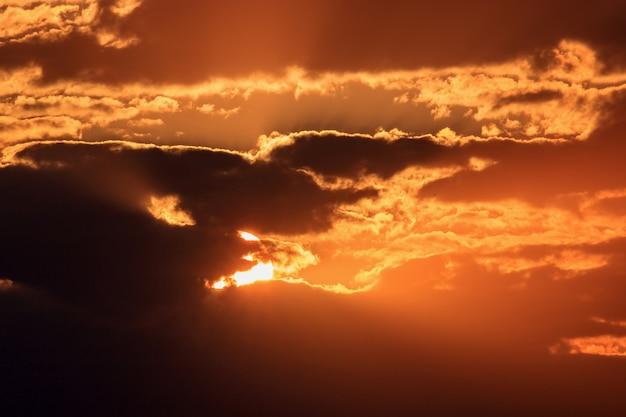 Cielo drammatico con nuvole scure e sole arancione al tramonto