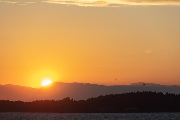 Drammatico paesaggio dell'alba a urla, izmir, turchia. bellissimo paesaggio di alba sfolgorante sul mare blu brillante e cielo nuvoloso arancione