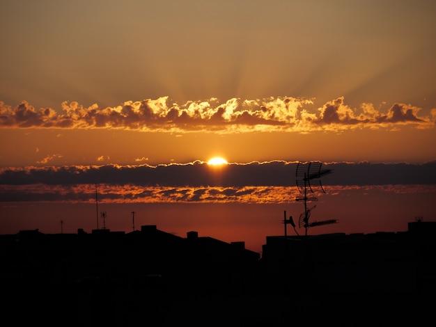 Cielo drammatico di alba sopra il paesaggio urbano dei tetti della città con il sole che splende attraverso le nuvole