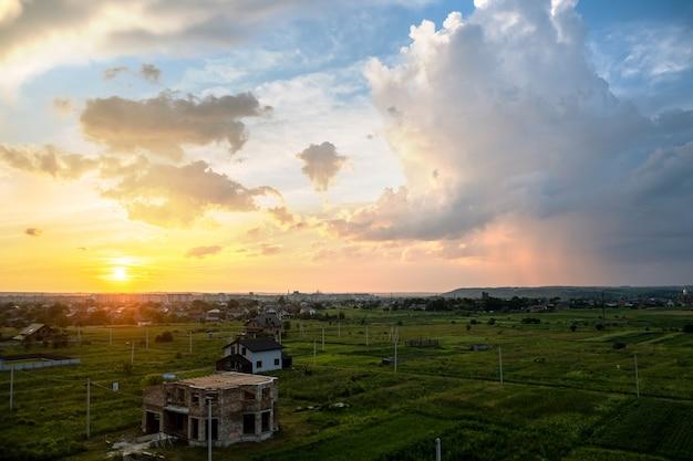 Drammatico paesaggio al tramonto della zona rurale con nuvole gonfie illuminate dal sole al tramonto arancione e dal cielo blu.