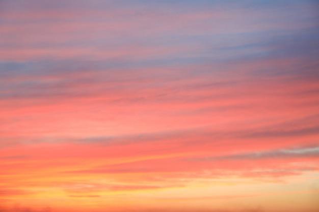 Fondo drammatico del cielo di tramonto con colore ardente delle nuvole, giallo, arancio e rosa, fondo della natura. bei cieli