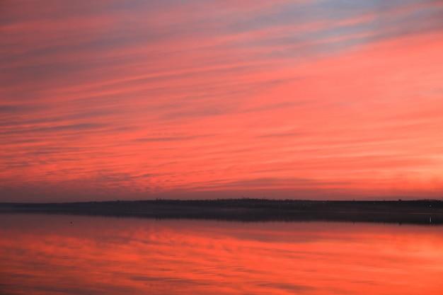 Fondo drammatico del cielo di tramonto con il fiume, le nuvole ardenti, il colore giallo, arancio e rosa, fondo della natura. bei cieli
