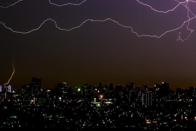 Fulmine drammatico di temporale sopra il paesaggio urbano alla notte